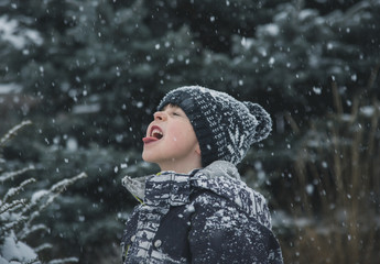 Playful boy sticking out tongue during snowfall
