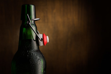 Close-up of green beer bottle against wooden background