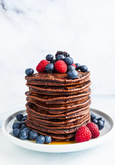 sweet American pancakes with fresh berries and sauce on the table