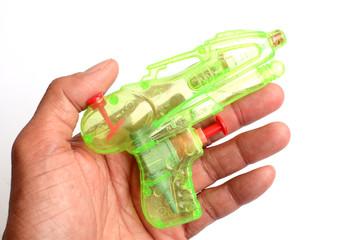 hand holding plastic green water gun on white background.