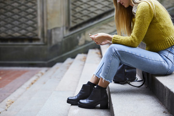 Low section of woman using phone while sitting on steps at park