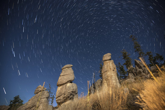 Low angle majestic view of rock formations against star trails during night at Badlands National Park