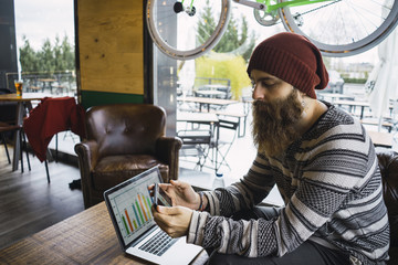 Hipster man using smart phone with laptop computer on table at cafe