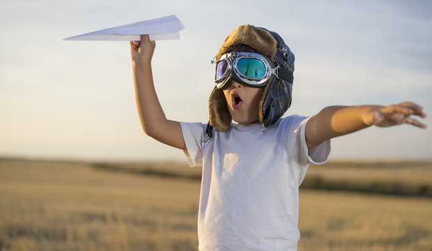 Fun Little boy wearing helmet and dreams of becoming an aviator while playing a paper plane at sunset