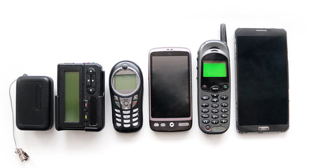 Old mobile phones and pagers isolated on white background