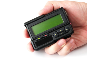 Old black pager in hand isolated on white background