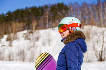 Picture of side view of athletic woman wearing helmet with snowboard looking at camera