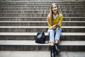 Portrait of smiling young woman sitting on steps at park