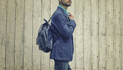 Casual wear: stylish bearded man in blue suit and jeans with leather backpack on wooden background.