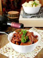 Meat stewed in red wine on a wooden table. Spanish cuisine meal