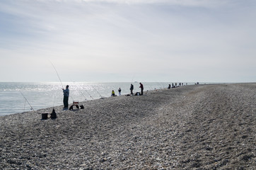 The fisherman is fishing on the shore of the Black Sea.