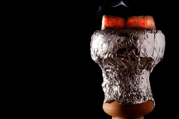 Cooked cup for smoking hookah in foil, burning red coals, white smoke, close-up