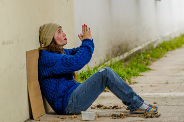 Outdoor view of homeless smiling woman begging on the street in cold autumn weather sitting on the floor with praying hands asking for something at sidewalk