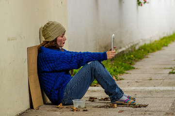 Outdoor view of homeless woman begging on the street in cold autumn weather sitting on the floor at sidewalk taking a selfie