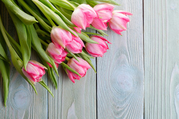 Bouquet of pink tulips on a wooden table, top view