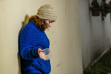 Outdoor view of lonely homeless woman on the street in cold autumn weather holding an empty plastic flask in her hand asking for money, at sidewalk