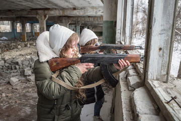 two girls child shoot from Kalashnikov rifles from the window of a destroyed building on the enemy in the war