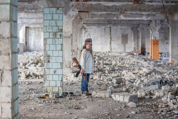 a little girl alone in an abandoned and ruined building with a Kalashnikov assault rifle and arms making her way to survive