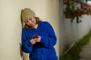 Outdoor view of homeless woman on the street in cold autumn weatherusing a celphone at sidewalk