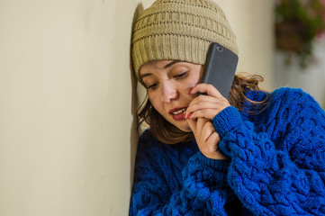 Portrait of lonely homeless woman on the street in cold autumn weather wearing a blue hoodie and using her cellphone at sidewalk