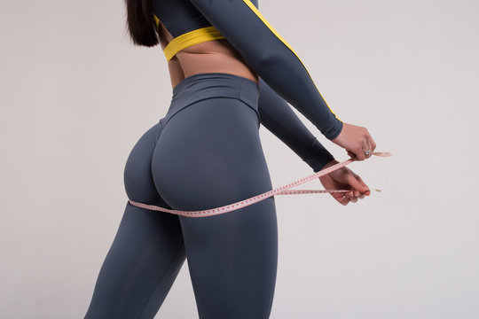 Strive for progress, not perfection. Closeup of fitness woman with tight hips and firm buttocks in workout leggings and measuring tape.