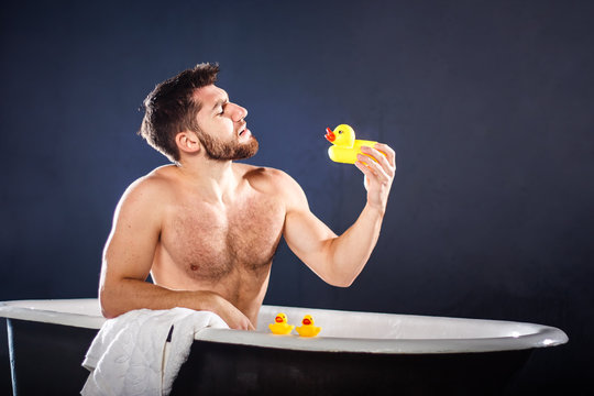 Handsome naked muscular adult happy man taking bath and playing with toy ducks, on dark-blue background