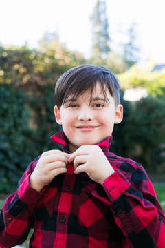 boy buttoning red flannel shirt