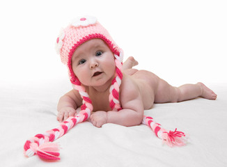 Funny female newborn with nice pink crocheted cap on white background. Happy baby girl with nice crocheted colorful cap on white blanket. Newborn wearing cute crocheted cap with flower ornaments.
