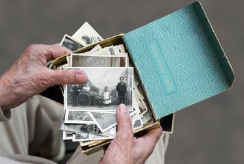 Senioren schaut sich alte Familienfotos an, Erinnerung an die Vergangenheit