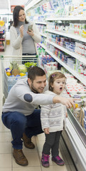 parents purchasing groceries in supermarket