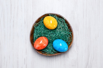 easter eggs in bowl on a wooden background
