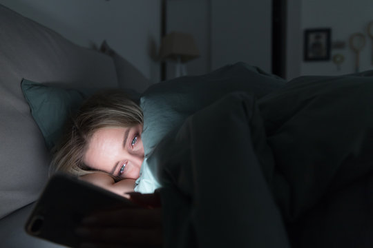 Sleepy tired woman lying in bed under the blanket using smartphone at late night, can not sleep. Insomnia, nomophobia, sleep disorder concept. Social network addiction