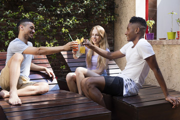 Multi-ethnic group of friends relaxed and drinking cocktails outside
