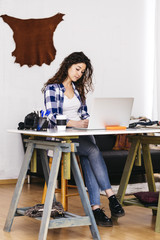 Spain, tarragona. Young designer in her workspace, working with a laptop.