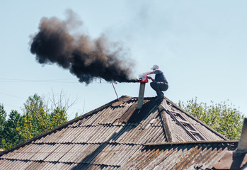 Chimney sweep man in work uniform cleaning chimney on roof