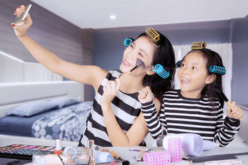Mother and child taking picture in the bedroom