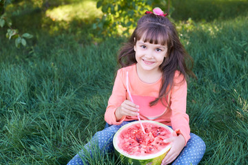 Small child. Bright green grass. Red juicy watermelon. Cute girl