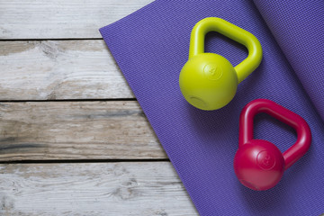 Kettlebell and yoga mat on table, fitness healthy and sport concept