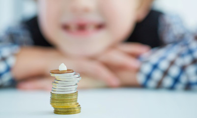 Smiling young boy with missing front tooth. Pile of coins with a baby tooth on top.