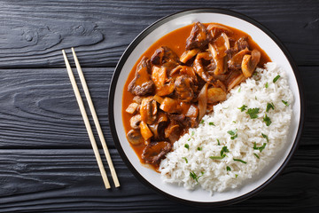 Japanese cuisine: Spicy beef with onions and mushrooms, as well as rice (Hayashi rice) close-up. horizontal top view