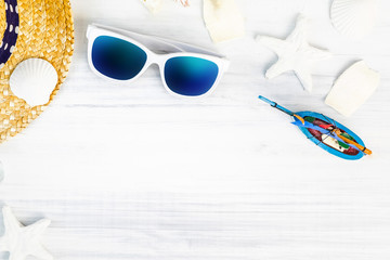 Wall Mural - Summer Beach accessories (White sunglasses,starfish,straw hat,glass bottle,shell) on white plaster wood table top view,Summer vacation concept,Leave space for adding text