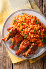 Porcion of African Jollof rice with fried chicken wings close-up on a plate. Vertical top view