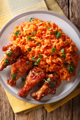 Classic Nigerian Jollof Rice with fried chicken wings close-up. Vertical top view