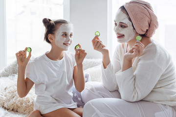 Mom with her daughter making clay face mask