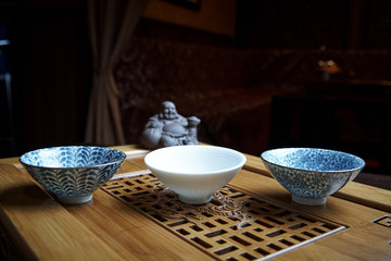Delicate bowls for tea ceremony on a wooden board with a statuette on a dark background.