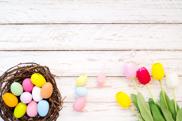Wall Mural - Colorful Easter eggs in nest with tulip flower on rustic wooden planks background. Holiday in spring season. vintage pastel color tone. top view composition.