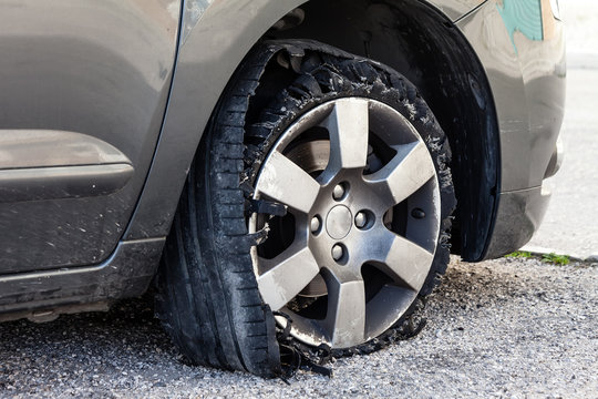 Destroyed blown out tire with exploded, shredded and damaged rubber on a modern suv automobile. Flat low profile tyre on an alloy rim, ripped open in pieces with visible interior.