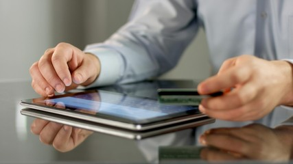 Male hands making online noncash payment on tablet, inserting bank card details