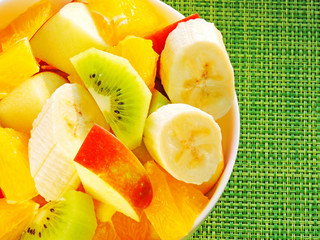Fresh juicy fruit salad in a white bowl