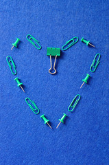 Green paperclips, folding clips and push pins on a blue background